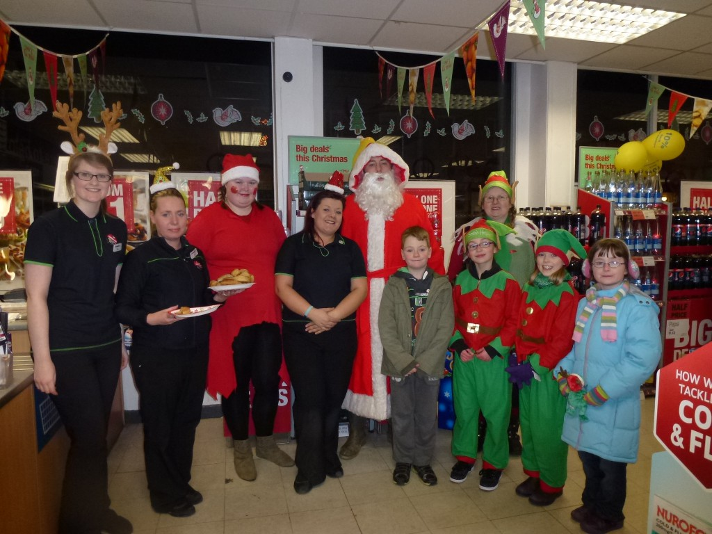 Staff at Alva Co-Op tempting Santa with mince pies